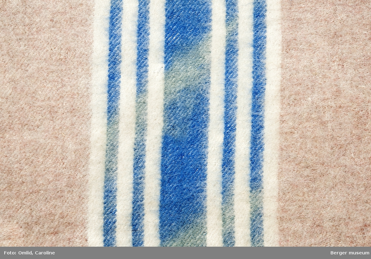 En prøve. Ensfarget gammelrosa med en bred blå stripe med to smalere striper på begge sider av den brede og hvite offwhite striper i mellom og utenfor de blå.