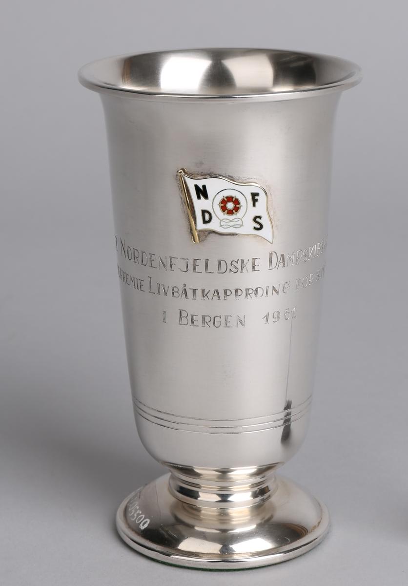 Sølvpokal fra Det Nordenfjeldske Dampskibsselskab, på sokkel med tekst inngravert samt emaljert rederimerke.