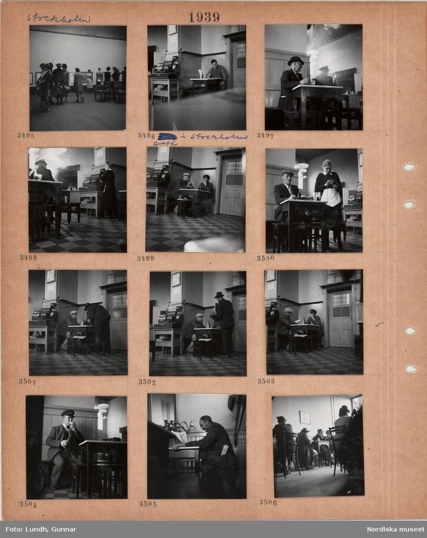 Motiv: Stockholm, utställningssal, tavlor på väggarna, besökare, café i Stockholm, kassaapparat, gäster sitter på pallar vid små kvadratiska bord, män som dricker öl och röker, servitris i svart klänning och litet vitt förkläde, en man läser tidning, gäster sitter på stolar, kvinnor och män.
