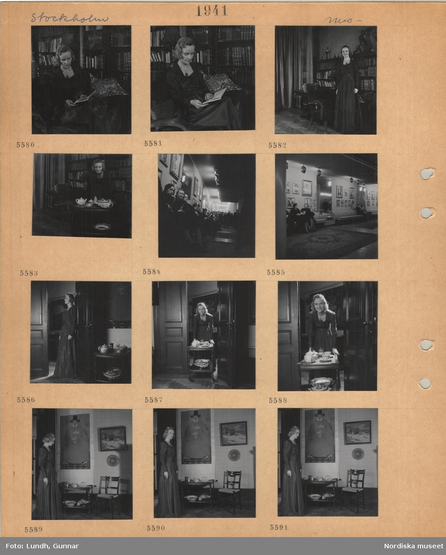 Motiv: Stockholm, modell i lång klänning som poserar, sitter i en soffa och läser en bok, bokhyllor, står vid soffa, vid tevagn, står i en dörröppning, kvinnor och män sitter i en sal med fotoporträtt på väggarna.