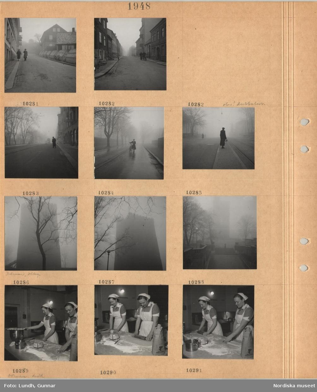 Motiv: Gata med flerbostadshus, fotgängare, hund, gata, gående, kvinna leder en cykel på regnvåt gata kantad av träd, kvinna väntar på en spårvagnsperrong, högt torn, Kärnan i Helsingborg, två kvinnor i hushållsuniformbakar bullar, kavlar deg, mjölpåse.