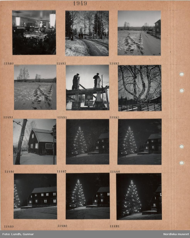 Motiv: Interiör bokhandel, hyllor med böcker, disk för julkort, kunder, två personer, den ena med sparkstötting, går på en snöig väg mellan träd, kulturlandskap i snö, två män snickrar på en byggnadskonstruktion utomhus, björk med flera stammar, fågelholk, trägärdsgård, skidor lutade mot väggen till ett bostadshus, julgran utomhus med tänd belysning, timmerhus med upplysta fönster, snö.
