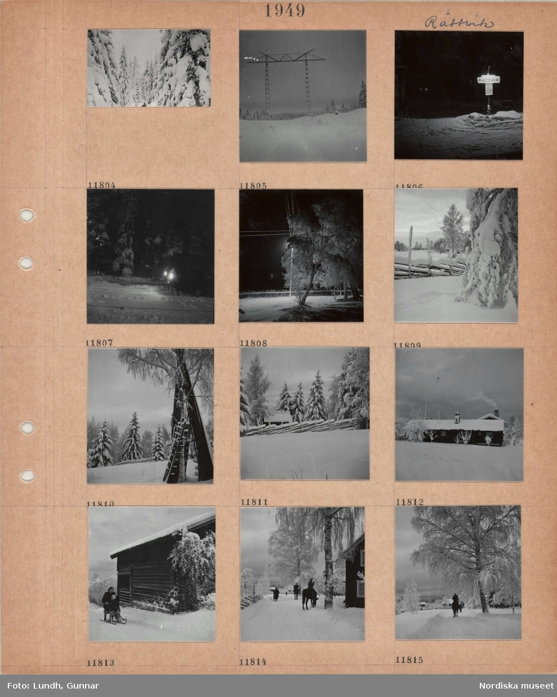 """Motiv: Rättvik, snötyngda barrträd, kraftledningsstolpar, belyst skylt """"Rättvik"""" vid hållplats, tänd gatlykta bakom snöigt träd, snöig trägärdsgård, hopsamlade hässjestörar lutade mot träd, lågt timmerhus i snö, kvinna och barn på en sparkstötting på byväg, ridande och gående personer på byväg,."""