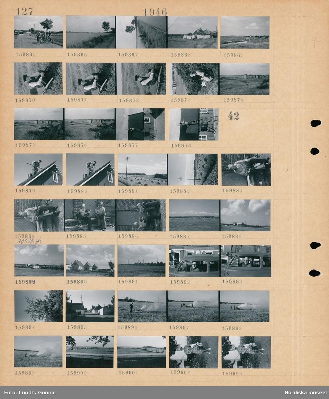"""Motiv: (ingen anteckning) ; Landskapsvy med cyklister på en väg, en man arbetar i ett dike, lakan hänger på tork på en tvättlina, landskapsvy med strand - hav och bebyggelse, en man sitter på en skottkärra, en kvinna sitter på marken, badhytter, en man tjärar ett tak.  Motiv: (ingen anteckning) ; En man tjärar ett tak, landskapsvy med åkrar med höhässjor, två män sitter och läser tidningen """"Vi"""", landskapsvy med åkrar, exteriör av hus, en man sitter i en bil, en person står på en stege och plockar frukt i ett träd, en man eldar växtdelar på en åker, porträtt av en kvinna som håller en blombukett."""