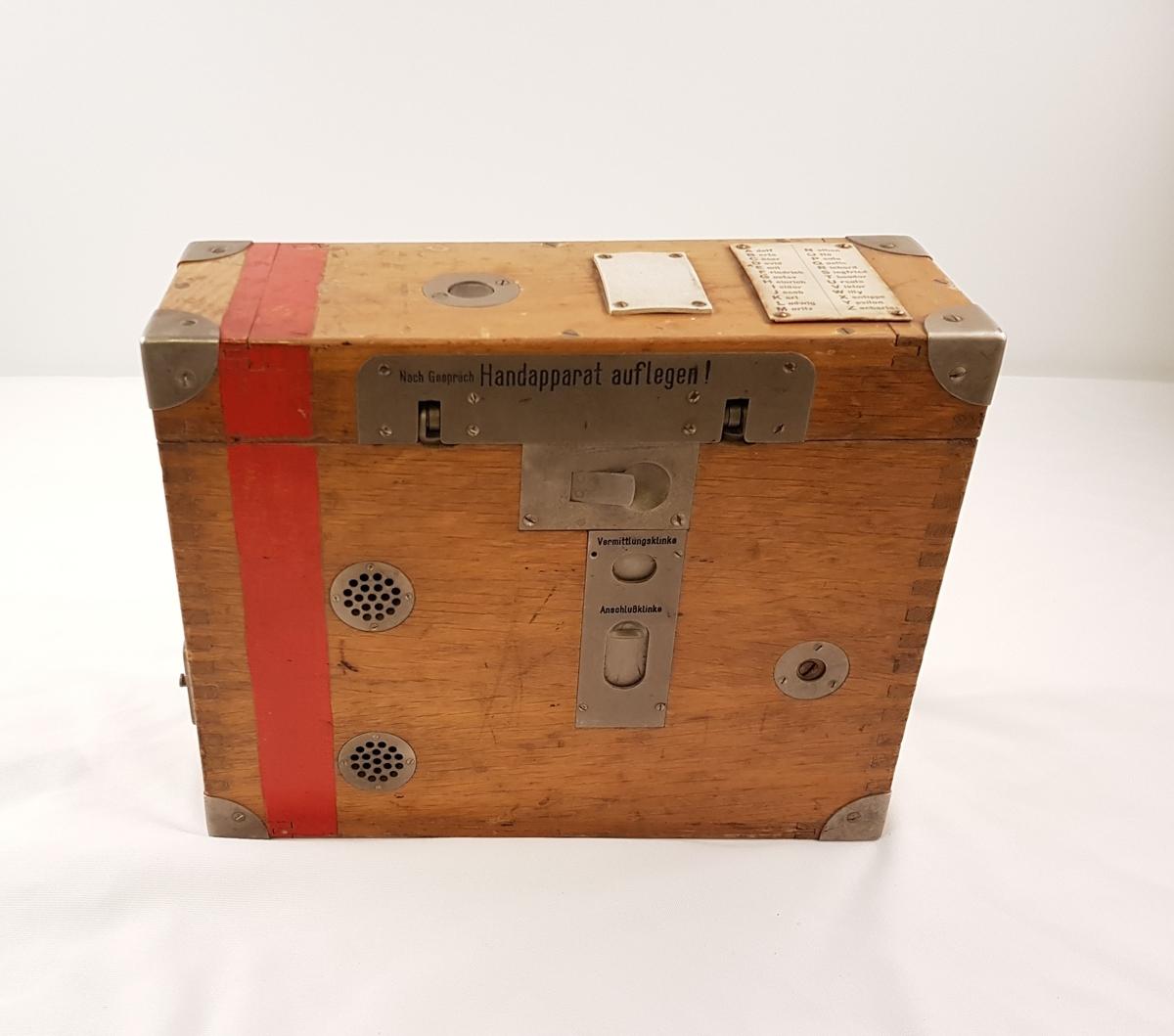 Felttelefon bestående av telfon og kasse i tre. Original påskrift.