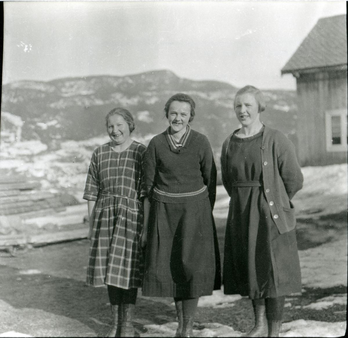 Tre kvinner står ute på tunet.