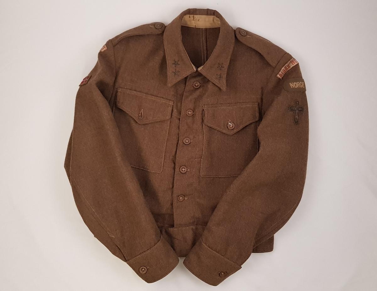 Grønn/brun uniformsjakke for løytnant . Jakken er merket med norsk flagg og Norge er brodert inn i jakken. På begge skuldrene er det Bjørn West-merke. På venstre arm er korset som indikerer at jakken har tilhørt en feltprest brodert inn.
