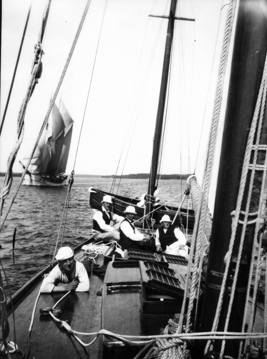 """Däcksbild, """"Ingvor"""". Liggande yrkesgasten, till höger Josef Johansson (ägaren), i mitten Werner Bengtzon, till vänster Jos. A. Johansson."""
