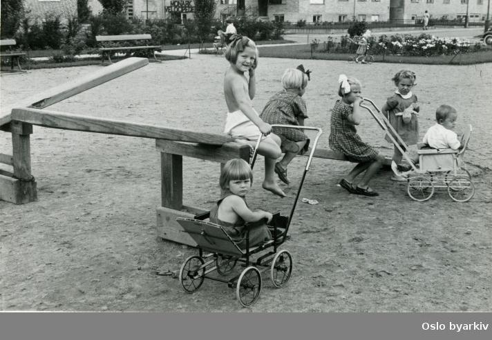 Barn på dumphuske og sittende i barnevogn ved en grusbelagt lekeplass. Blokkbebyggelse i bakgrunnen med reklameskilt for Monark Velosiped (Veltepetter) over inngangsparti.