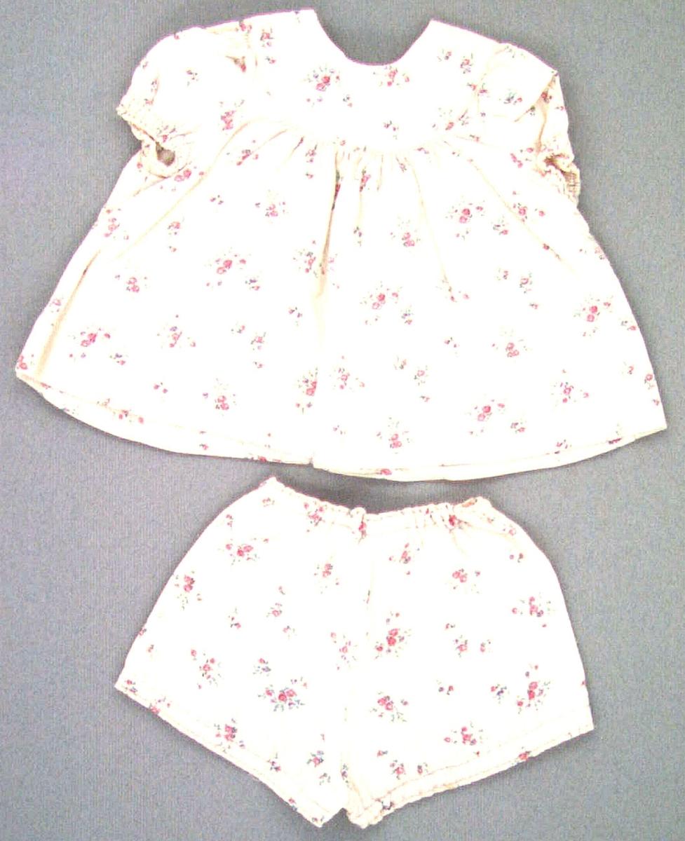 Dockklänning av rosa silkesflanell med tryckta små blommor i rött och grönt. Klänningen har fyra tryckknappar i ryggen, rundat ok samt puffärmar med resår i ärmsluten, Till klänningen finns ett par underbyxor av samma tyg. Tyget på byxorna något slitet. Klänningens längd: 270 mm, bredd 440 mm. Byxans längd: 190 mm, bredd 300 mm.