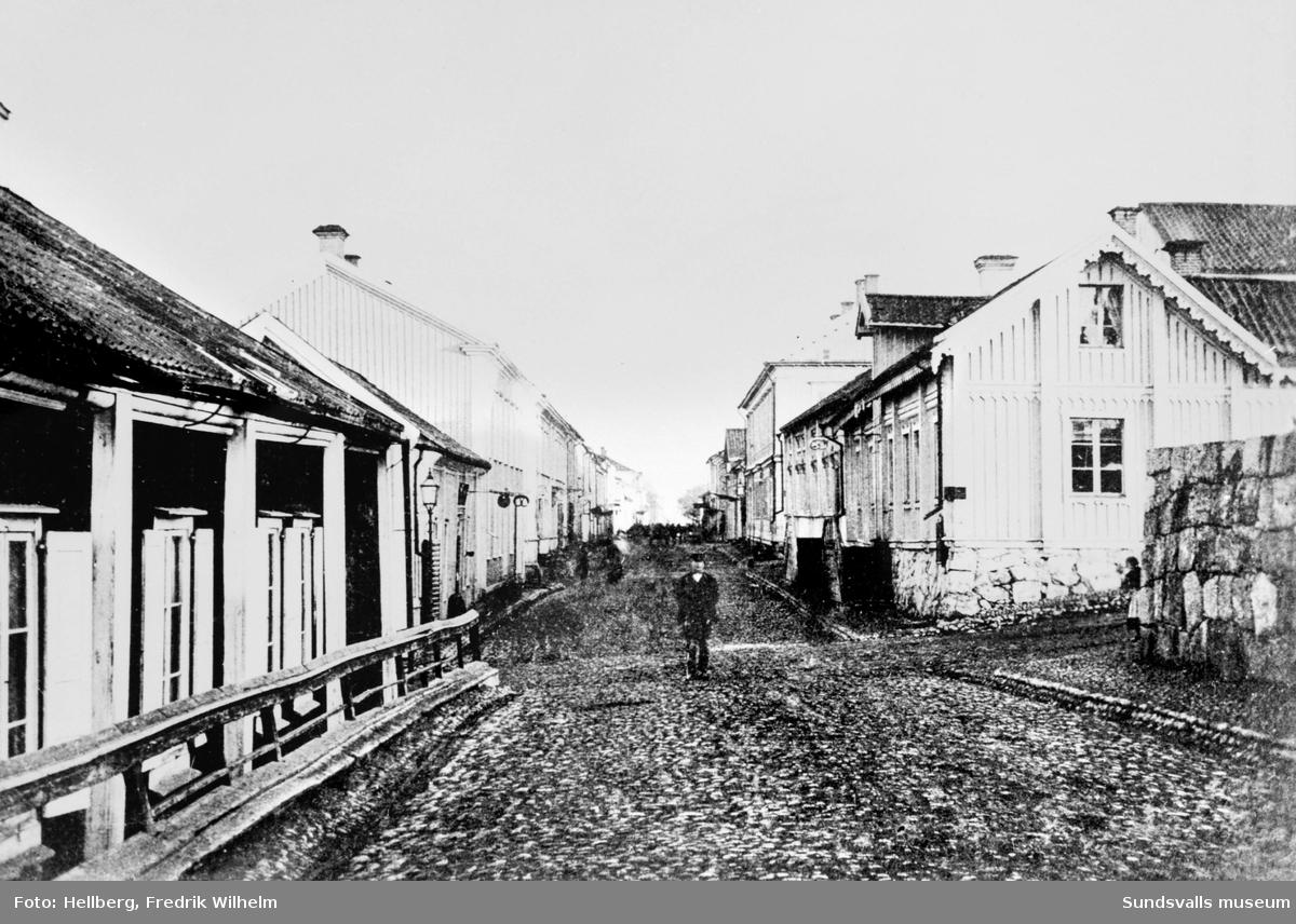 Sundsvalls stadskärna före branden 1888. Storgatan österut från Badhusgränd/Stora Nygatan, till höger FW Hellbergs bageri och fotoateljé som brann 1878. Kyrkomuren ses närmast till höger.