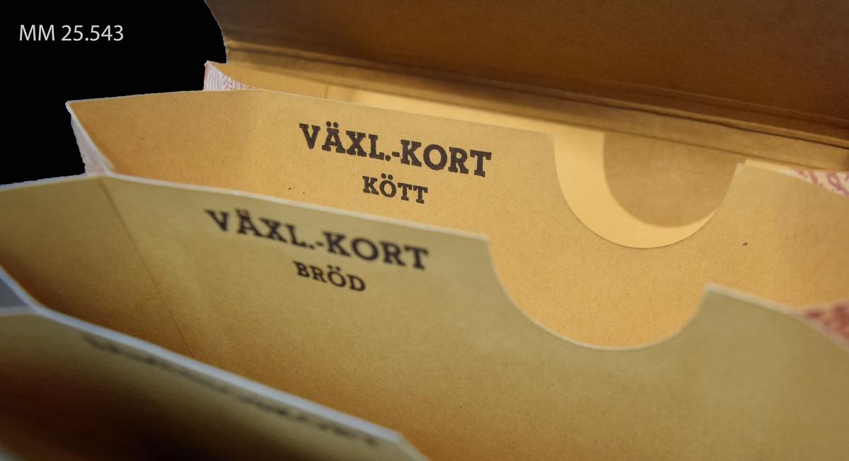 Brunt dragspelskuvert. En flik går att vika över framsidan för att stänga kuvertet. Text på fliken: RANSONERINGSKORT. I kuvertet finns fyra separata fack med plats för ransoneringskort märkta: SAMLINGSKORT, VÄXL.-KORT BRÖD, VÄXL.-KORT KÖTT och DIVERSE. På framsidan anteckning i blyert 109 eller A09.
