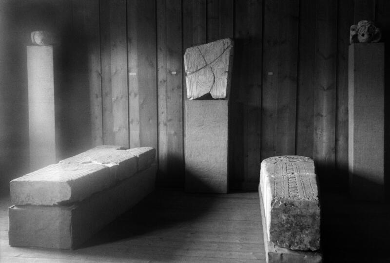 Gravsteiner fra middelalderen ligger på utstilling i et gammelt tømmerhus. (Foto/Photo)