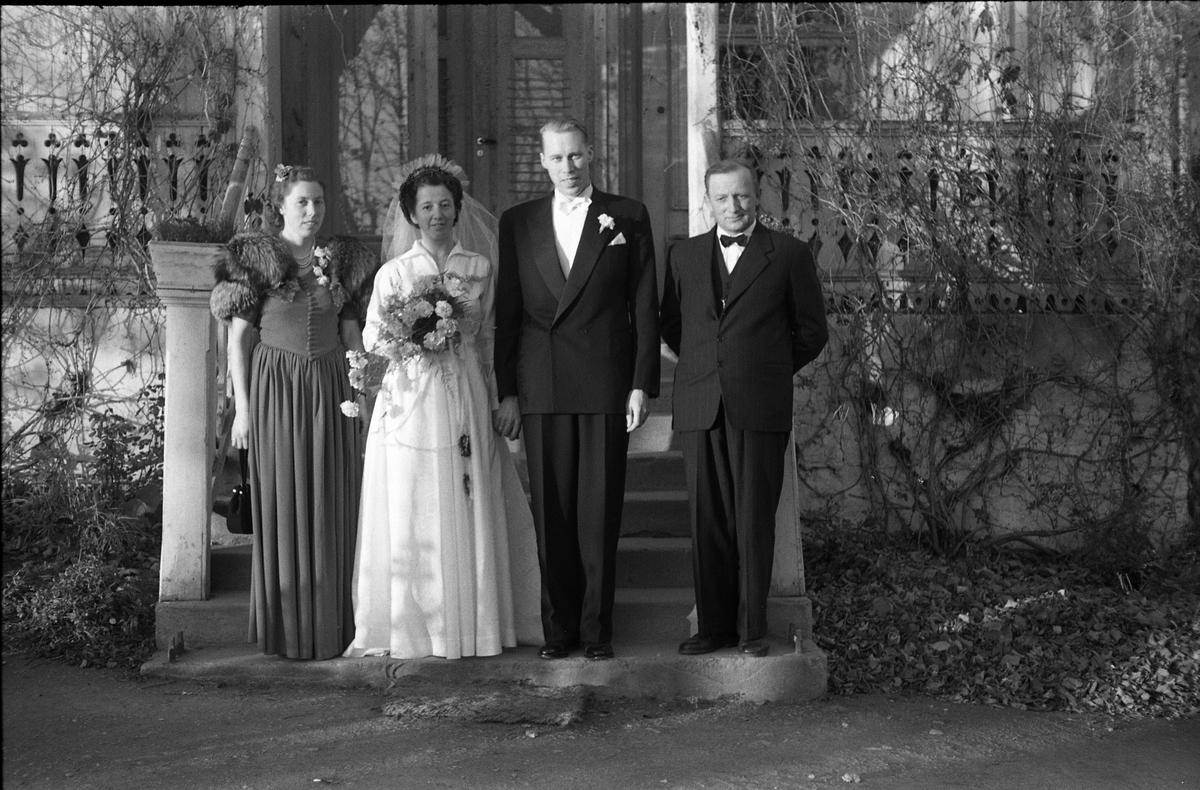 Helfigurs portrett av et brudepar, og trolig deres forlovere. Brudeparet antas å være Gerd Egge og Håkon Jevne. Hvis dette stemmer er forloverne Nora Fjørkenstad og Håkon Ekern. Bildet antas tatt foran Hoff Gjestgiveri 21.oktober 1950.