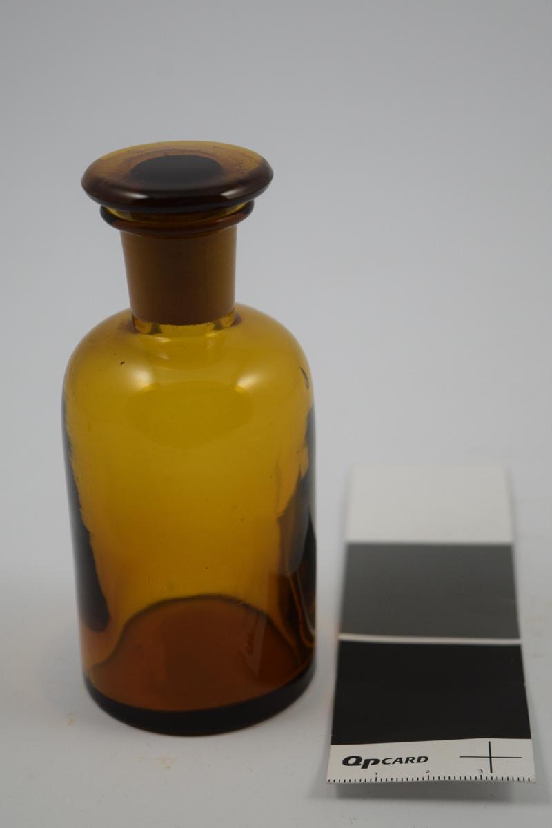 Brunt glass med glasspropp smal hals. Brukes til oppbevaring av flytende.