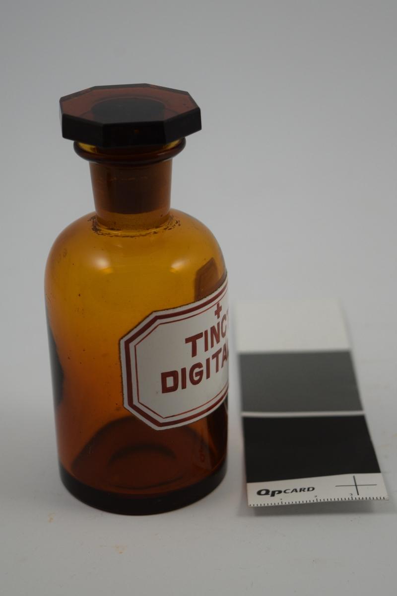 Glasskrukke med glasspropp. Etikett hvit med rød skrift. Ett kors, betyr at innholdet er giftig. Tinct. Digitalis: ble produsert på apoteket, digitalis tinktur. Hjertemedisin.
