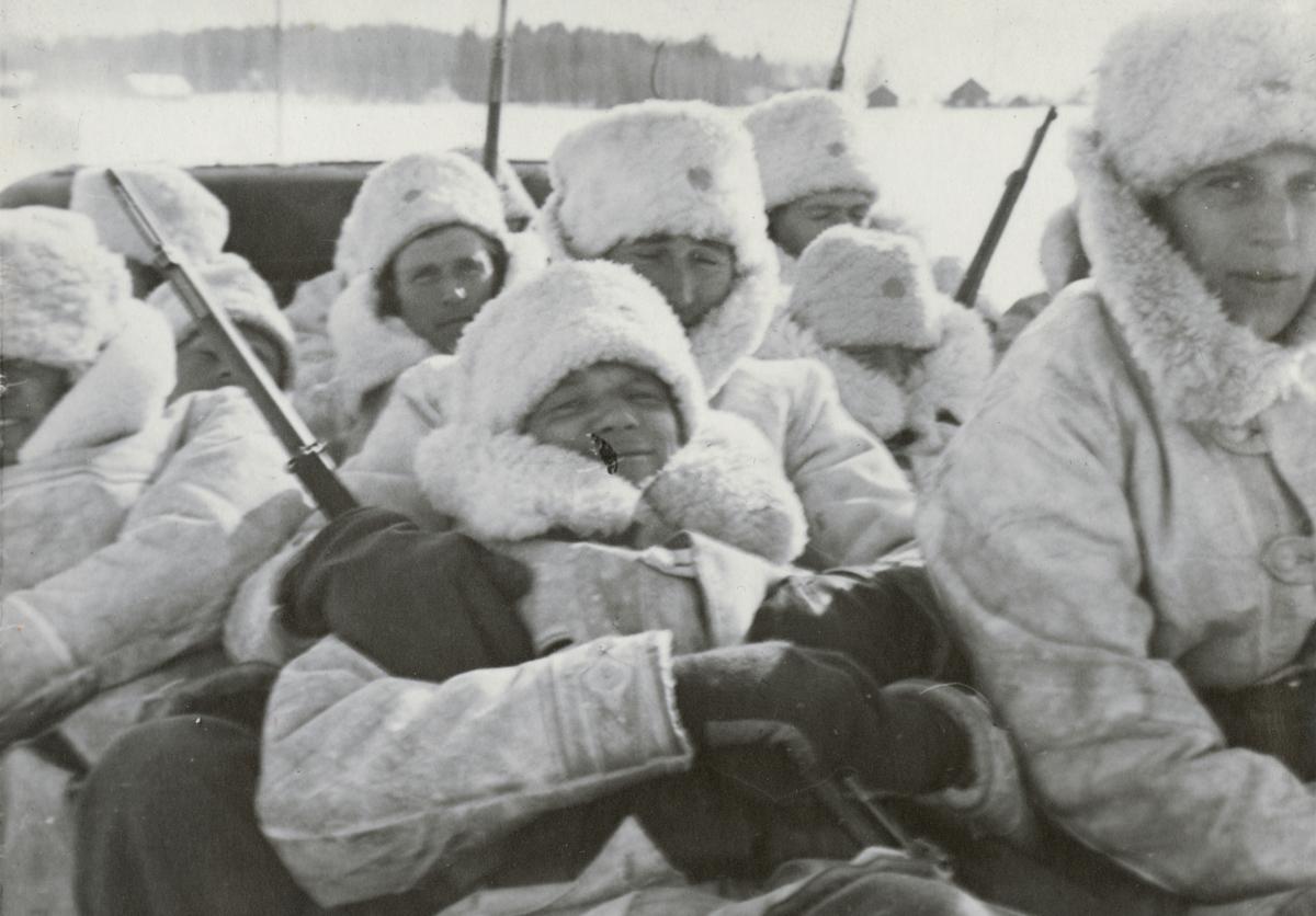 Soldater på lastbilsflak under transport.