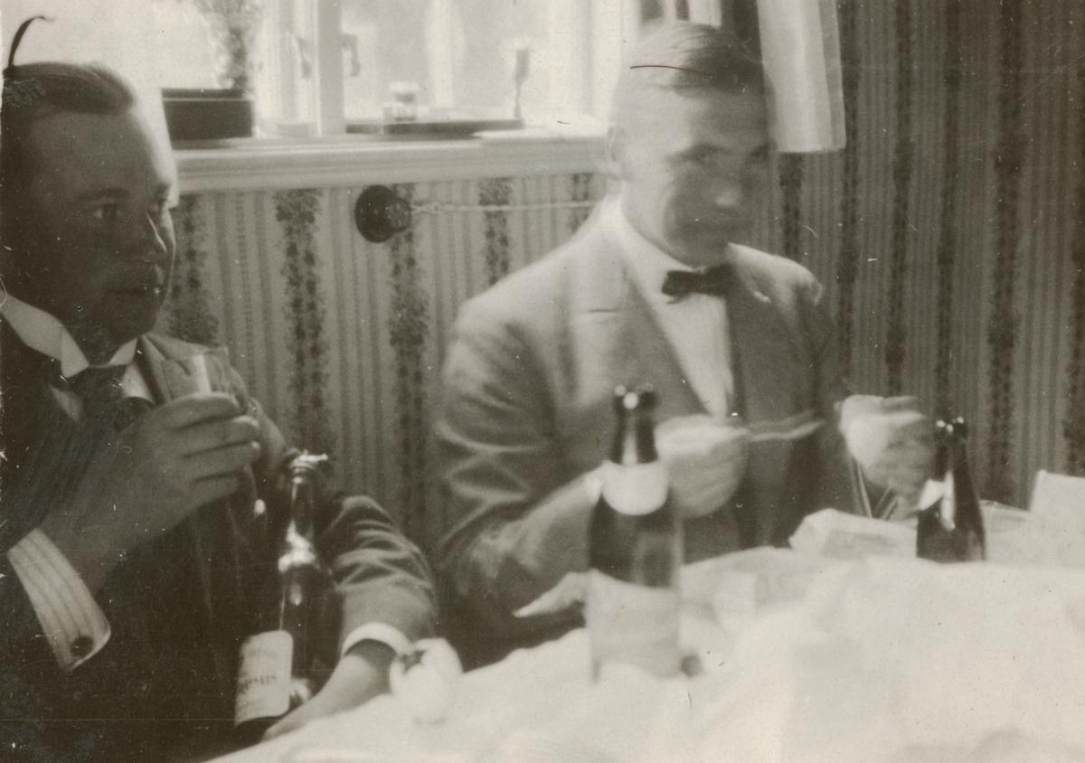 Två män vid matbord.