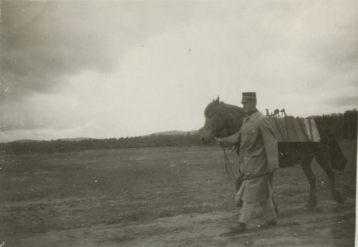 Soldat leder häst på övningsfält.