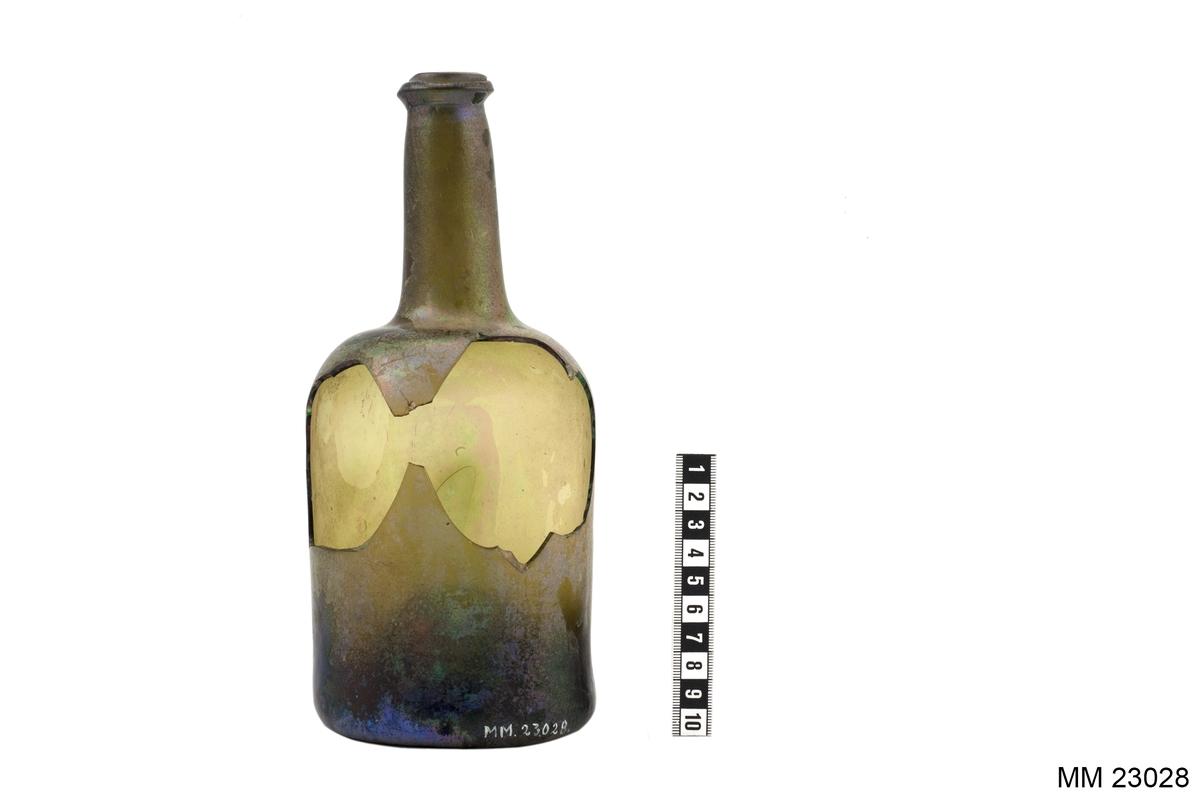 Flaska, sjöfynd från Nya Riga. Den trasiga flaskan har ett större hål strax nedanför flaskhalsen. Flaskan är iriserad. På delar av flaskan har iriseringen nötts bort. Flaskbotten är försedd med en urgröpning om cirka 45 mm i djup. På flaskans mitt finns en större luftblåsa. Hela flaskan är aningen skev. Öppningen på flaskhalsen är något ojämn.