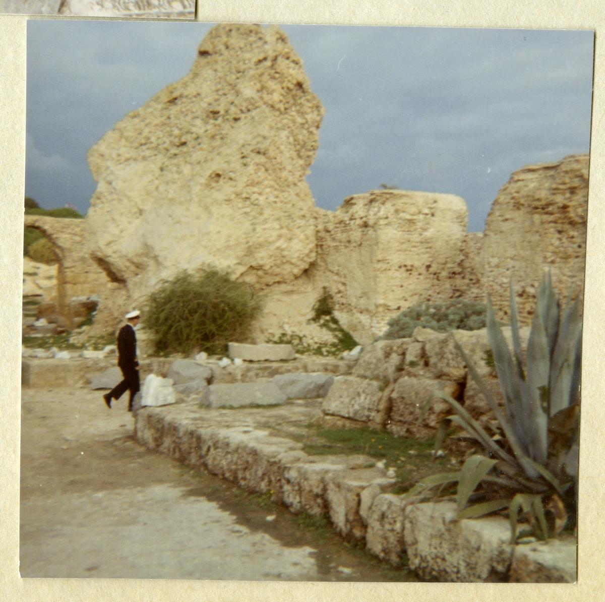 Bilden föreställer en uniformsklädd bestättningsman från minfartget Älvsnabben gående igenom Karthagos ruiner i samband med långresan 1966-1967.