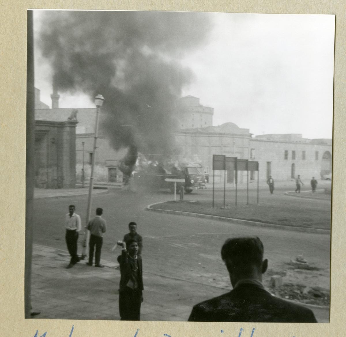 Bilden föreställer en buss, vilken det kommer kraftig rök ifrån. På bilden syns även byggader och människor i omgivningen. Bilden är tagen i samband med minfartyget Älvsnabbens långresa 1966-1967.