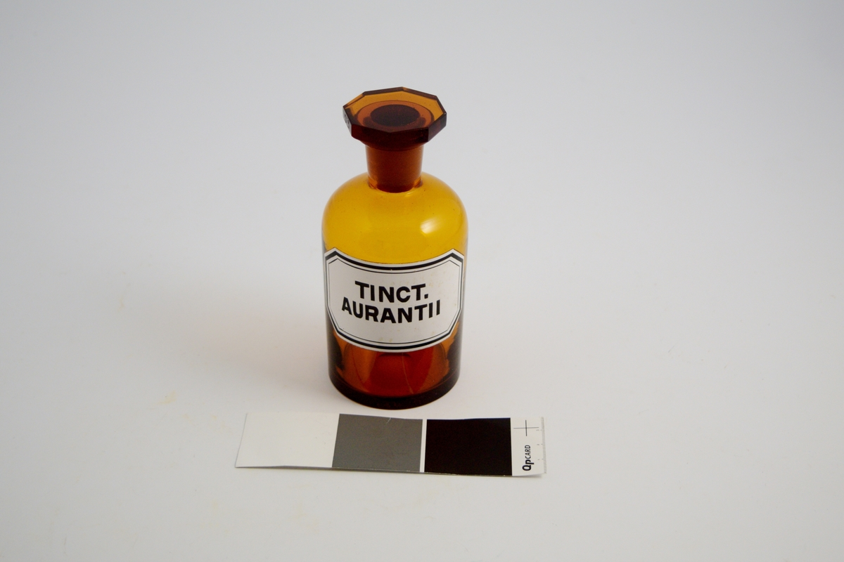 Brun glasskrukke med glasspropp. Hvit etikett med sort skrift. Tinkt. Aurantii vil si: Tinktur av pomeranskall. Dette ble brukt som smakstilsetning i flytende legemidler med mer.