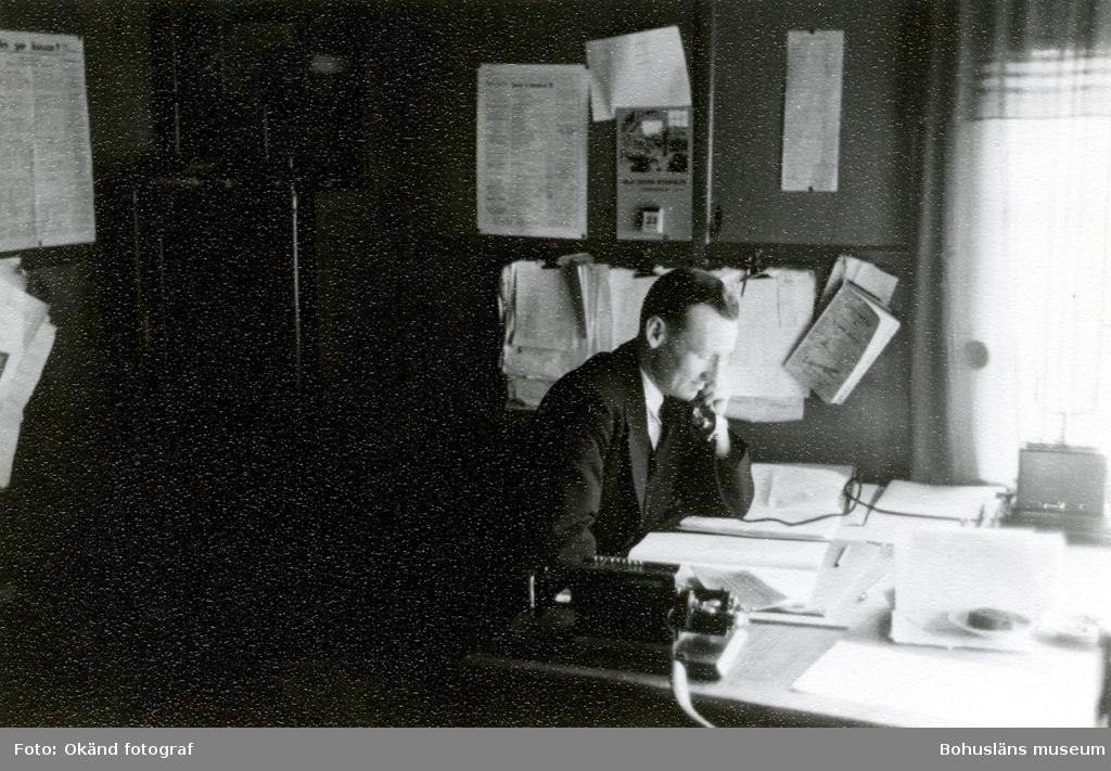 En man pratar i telefon sittandes vid ett skrivbord på ett kontor
