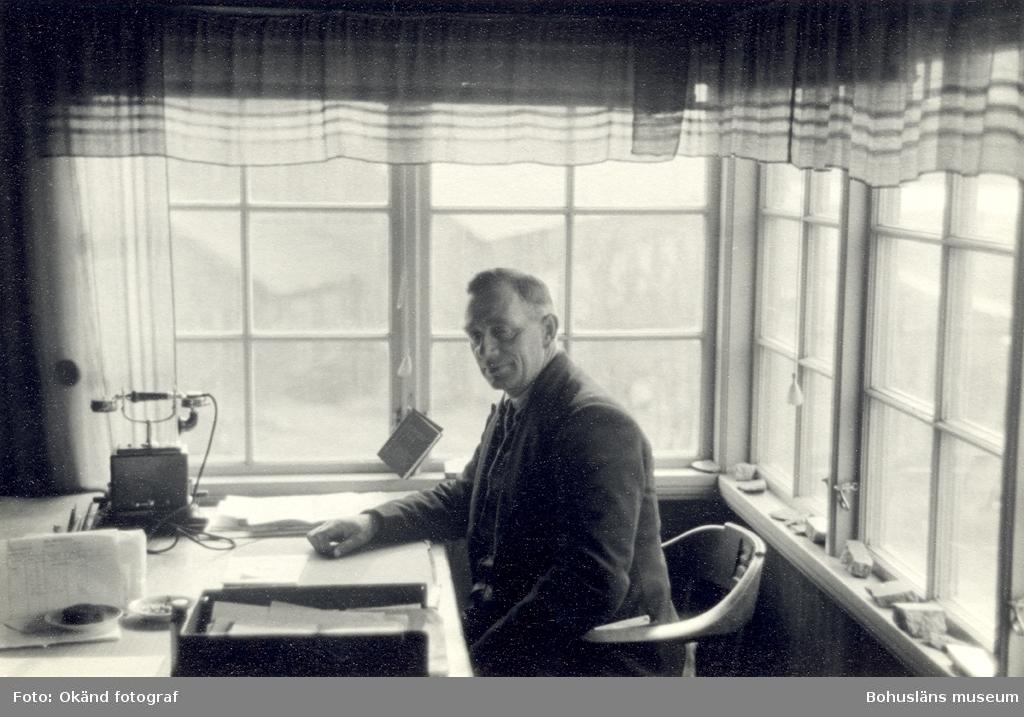En man sitter vid ett skrivbord placerat vid fönster, i fönsternischerna ligger stenar