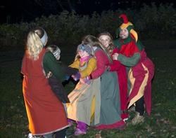 Fem barn i middelalderklær får hjelp av en narr til tautrekking.