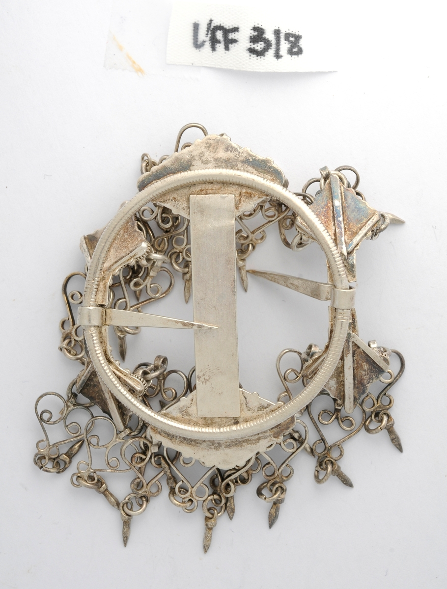 Sølje, hornring i  sølv, ingen stempel. På baksida støypt ring med seks pålodda plater i ulike størrelsar. På framsida er platene dekorert med filigransarbeid og hjarteforma heng. Stolpe midt på, og med ei tann (nål) på kvar side.