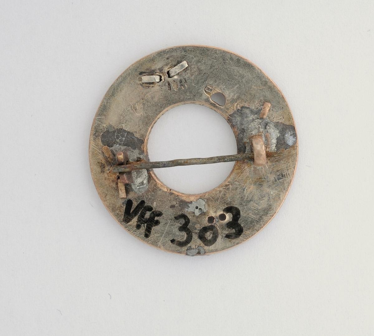 Sølje, rund plate dekorert med filigransarbeid. Utydelege stempel (TT og IR)? bak. Vanleg nål.