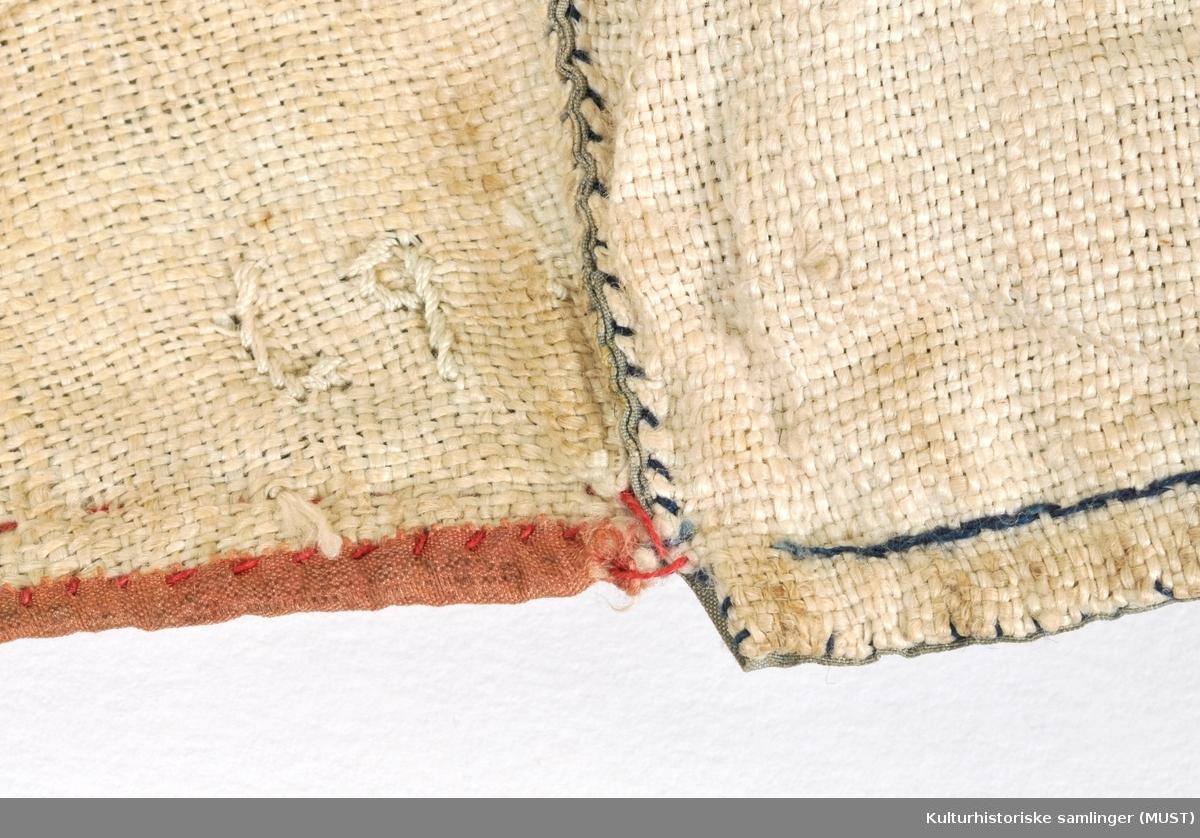 Luen er sydd av silke, brosjert lys blå taftbunn med blomsterbrosjeringer i ulike farger. Luedelene er sydd sammen med spilesøm. Fór av løsvevet linlerret. Pannestykke er kantet med rosa taftbunn som er lerretsvevd, 0,8 cm br. påsydd med rød silketråd. Knyttebånd mønstervevd av bomull.