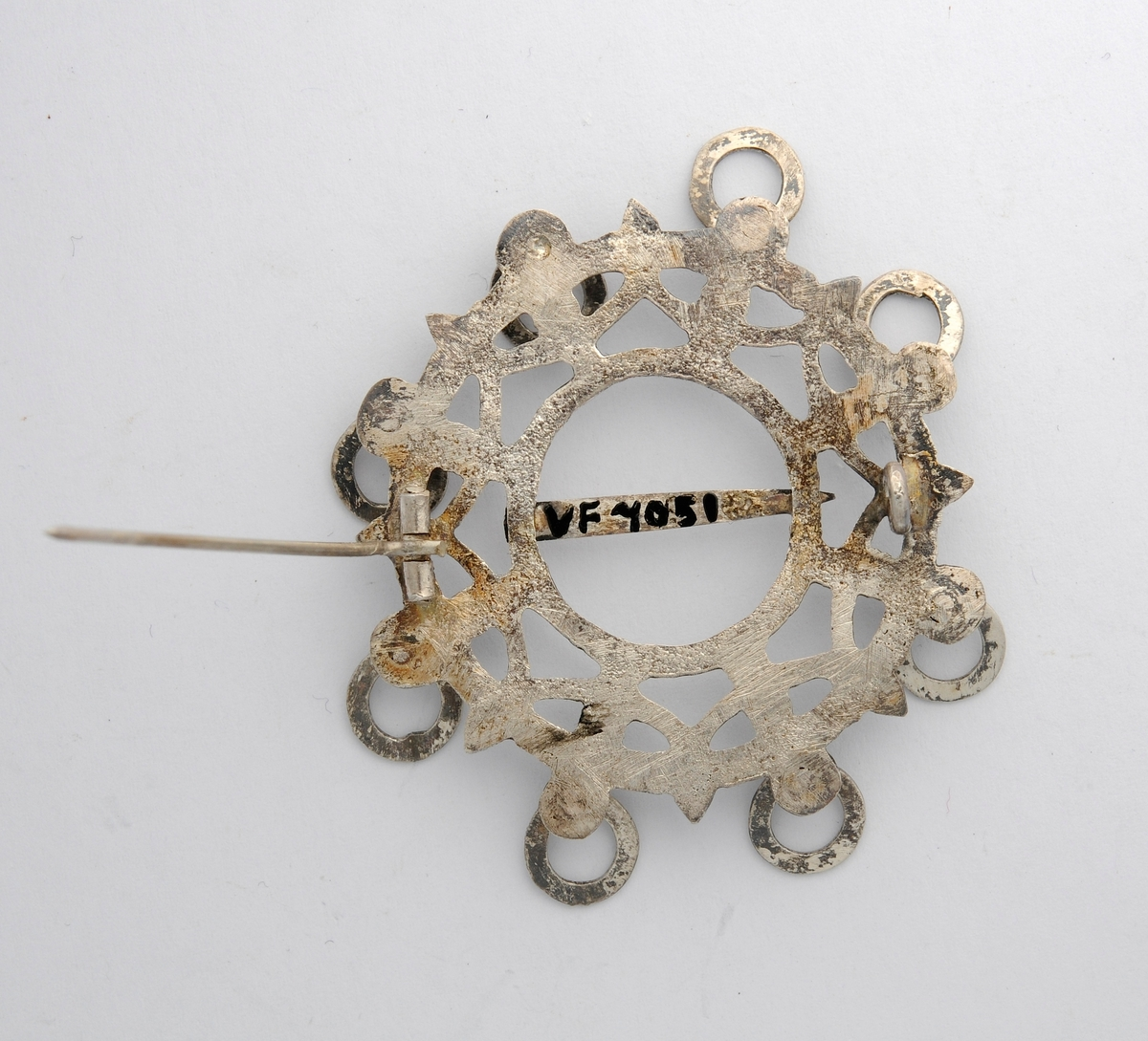Sølje i sølv (utan stempel) støypt og med mønster på framsida. Rundt kanten åtte hemper med ringar i. Tanna er etterlikna etter gamle søljer, men fastlodda. Moderne nål på baksida.