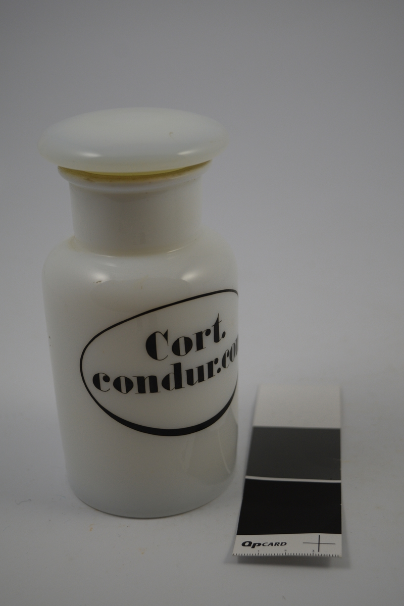Hvit porselenskrukke med propp. Påsatt etikett med sort oval ramme. Cort. Condur. conc. betyr kondurangobark, oppkuttet. Krukken er tom. Denne typen krukke ble brukt til oppbevaring av pulver.