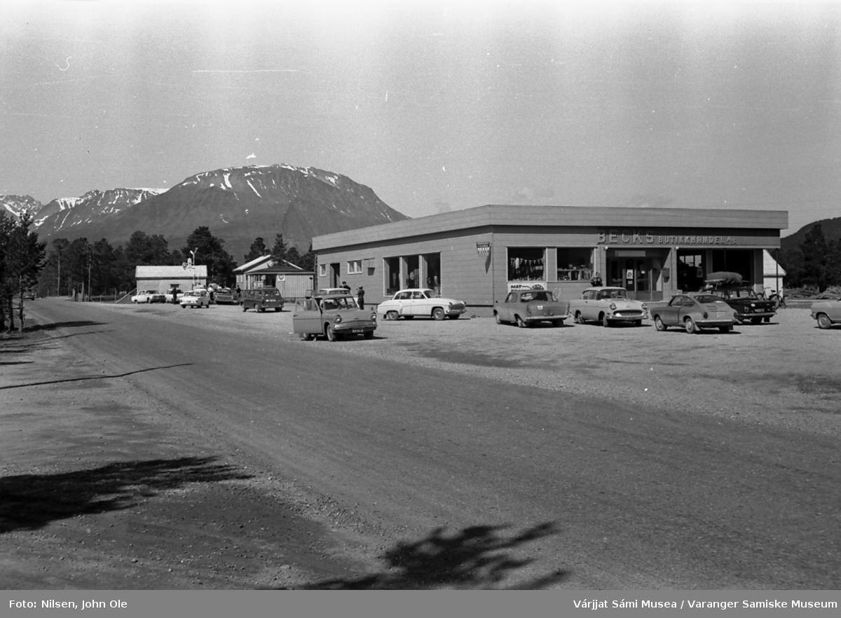 BECKS BUTIKKHANDEL AS i Skibotn. Biler står parkert utenfor. Vei i forgrunnen, fjell med snø på toppen i bakgrunnen. 17. juli 1967.