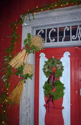 Julenek med rød sløyfe og kranser av grønt bar henger på en gammel dør.
