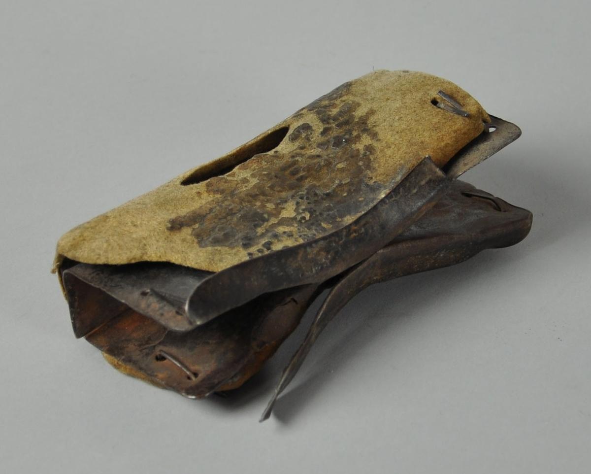 Består av to metallbiter som er bøyd og satt sammen slik at det passer til å få grep rundt. Rundt metallet er det et lag med stoff / tøy for å vern mot varme.