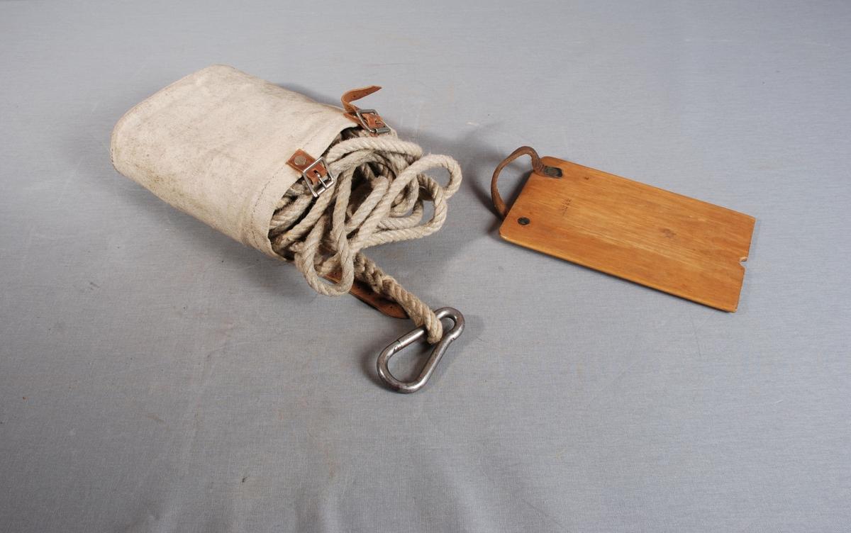 Branntau i oval  avlang lerretspose med åpning i toppen, lukkes med to lærreimer. Branntauet/redningstauet ligger oppvundet i posen, i spleiset tauende en carabinkrok. Tilhørende vindebrett for opprulling av branntauet etter bruk. Lærhåndtak.