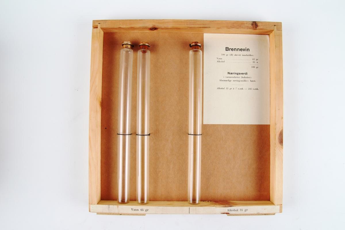 Ramme med tre reagensrør som illustrerer næringsinnholdet i brennevin