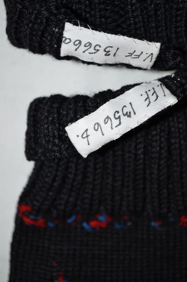 Fingervotter (a+b) glatt strikket i svart ull. Vrangbord i 2 rette og 2 vrange. Rosesøm på håndbaken i to nyanser rødt, to nyanser grønt, to nyanser blått og rosa.