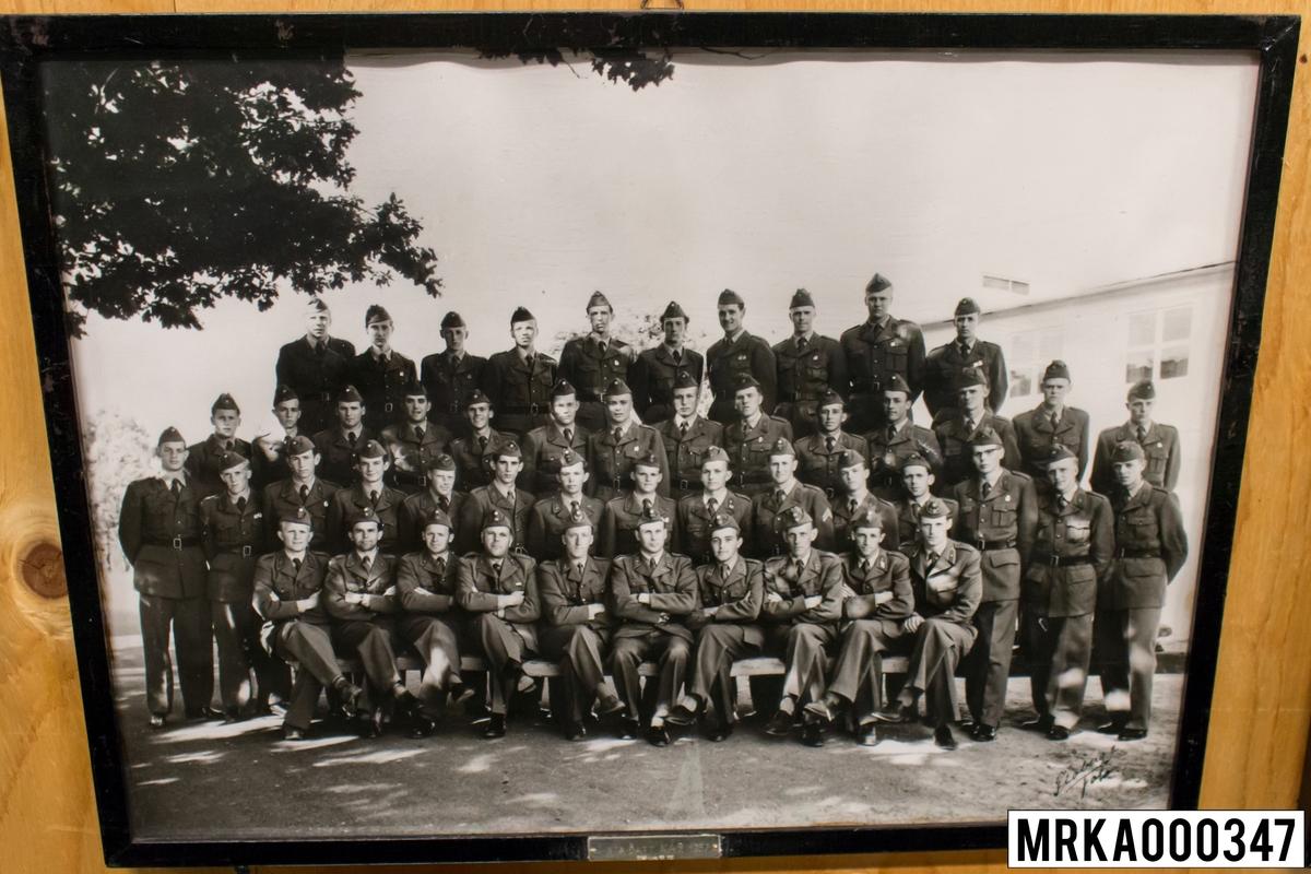 Fotografi taget på befäl och soldater som genomfört grundläggande soldatutbildning på 1:a Batteriet KA 2. Fotografiet taget på övre plan Gräsvik KA 2. Flobergs Foto 1957.