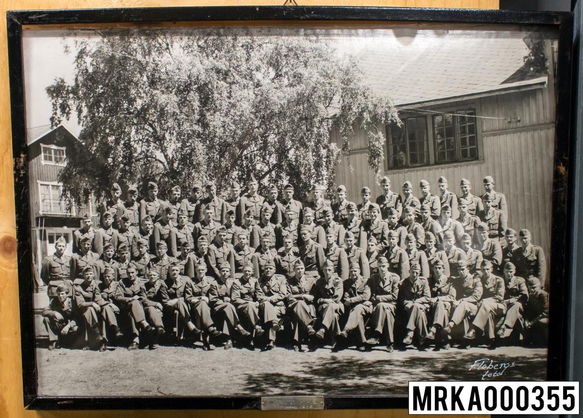 Fotografi taget på befäl och soldater som genomfört grundläggande soldatutbildning på 1:a Batteriet KA 2. Fotografiet taget på övre plan Gräsvik KA 2. Flobergs Foto 1959.