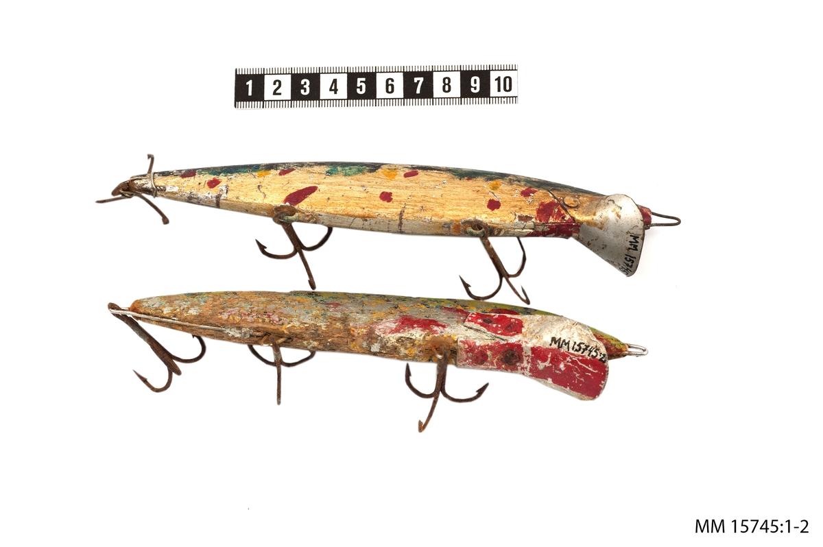 Fiskedrag av trä och järn. Draget i form av en fisk. Träkroppen målad i silvergrått och svart med stänk av grönt, rött och gult. På kroppens buk är tre, trehulliga krokar fästa. Vid framdelen är en skål fäst så att draget sjunker djupare. Troligtvis ett gäddrag.