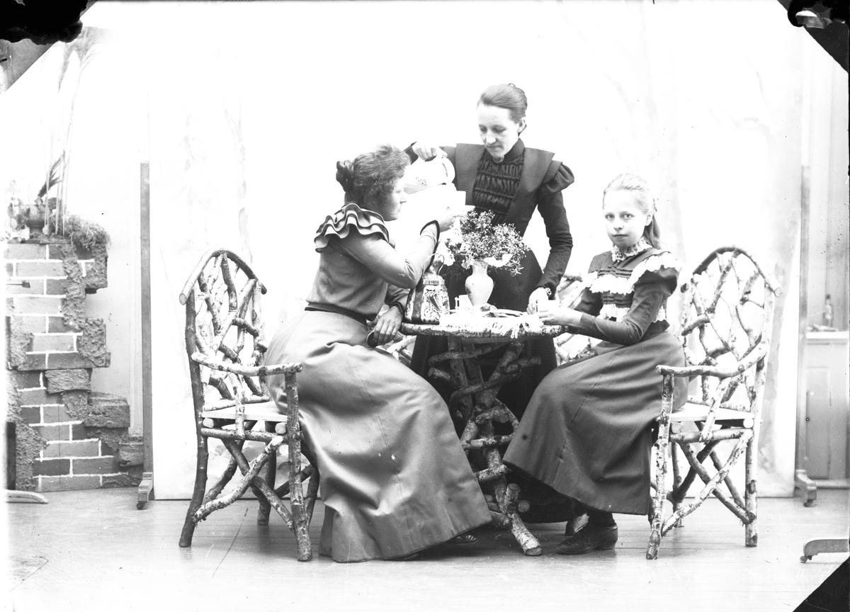 b926dcea To voksne kvinner og ei ungjente ved et kaffebord. Ingen av personene er  identifisert.