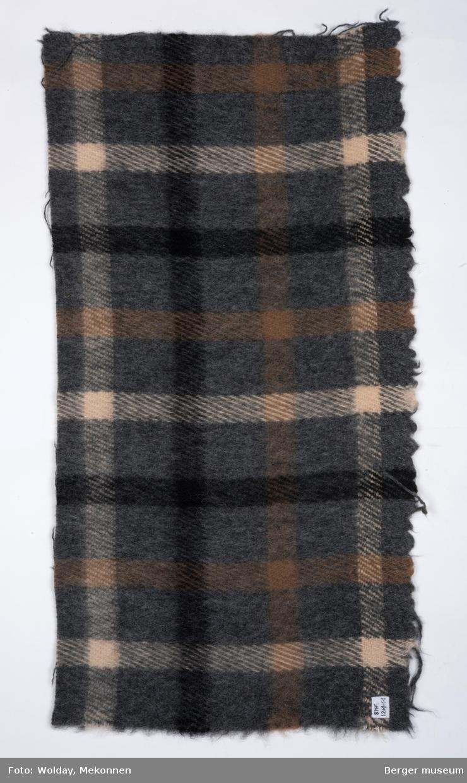En pleddprøve i rutemønster. Prøven har klippede kanter, men ene langside jarekant. Mønsteret karakterisereres av kryssende striper i sort, brun og offwhite med jevne mellomrom, på en grå bakgrunn. Fargeholdningen er duse grå og brune toner.