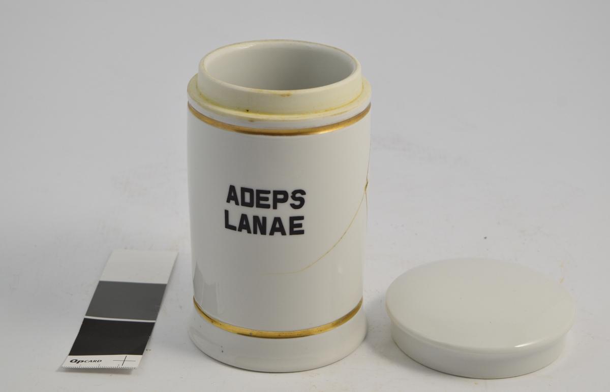 Sylinderformet porselenskrukke med porselenslokk. Hvit med gulldekor linje langs toppen og bunnen. Påtrykket med sort skrift ADEPS LANAE, som betyr ullfett. Krukken ble brukt il oppbevaring av ullfett, som ble brukt til produksjon av diverse salver, blant annet Lanolin.
