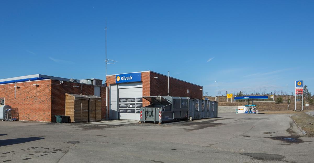 Statoil Dal. Bensinstasjon med vaskehall og søppelcontainere. I bakgrunnen pumpeanlegget for truck og et veiskilt Statoil.