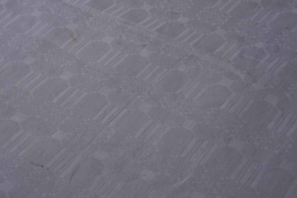 Hvit lin dreilveving. To bredder sydd sammen på midten. Smal fall på kortsidene.