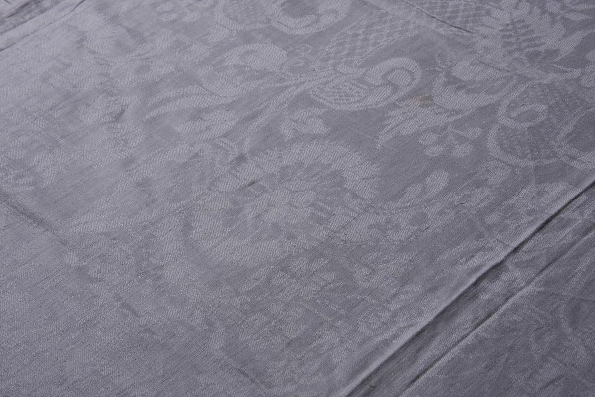 Hvit lindamask med bred kantbord på siden, med blomsterranker. På midten stort solsikke-mønster og båndmotiver med gitterverk-mønster. Smal fall på kortsidene.